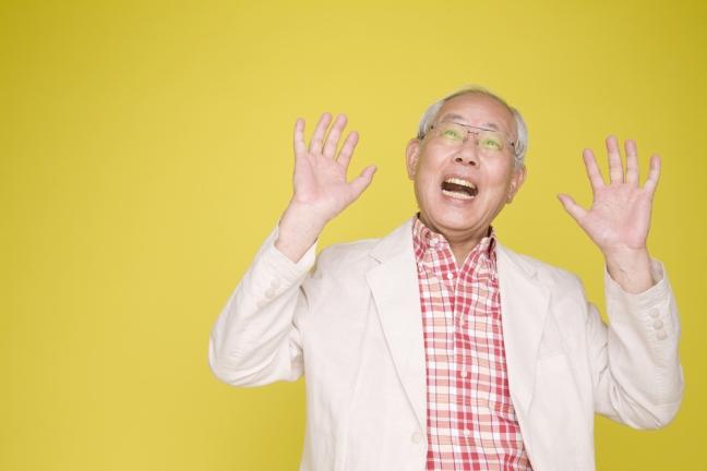 Bild zum Thema Persönlichkeit: Älterer Herr asiatischer Herkunft mit freudig überraschtem Gesicht, die Hände erhoben, vor gelbem Hintergrund