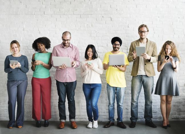 Personen unterschiedlicher ethnischer Herkunft, jede schaut auf ein mobiles Endgerät
