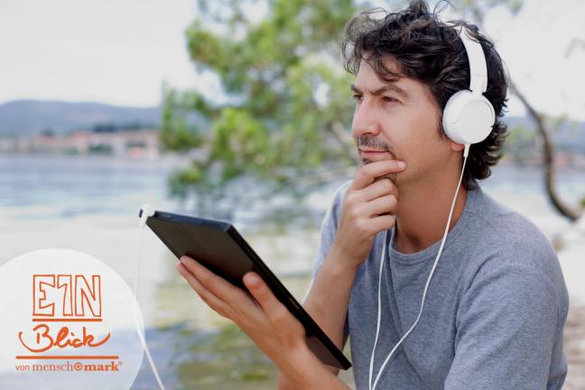 Bild eines Mannes, der mit Tablet und Kopfhörer am See sitzend einen Podcast anhört