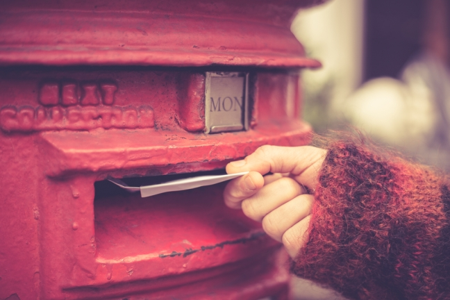Bild einer Frau, die einen Brief in einen Briefkasten steckt. Posting vor der Zeit der sozialen Netzwerke.