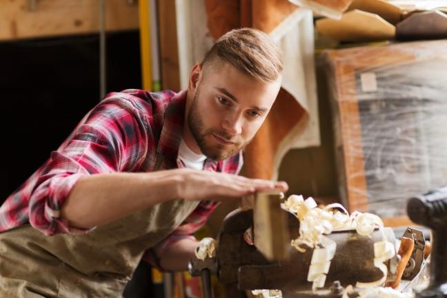 Bild eines jungen Schreiners, der die Oberflächenqualität eines Holzstückes prüft
