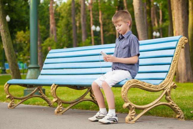 Kleiner Junge, auf einer PArkbank sitzend, hört Musik über sein Smart Phone