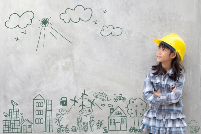 Bild eines kleinen Mädchens mit BAuhelm, das auf eine Wand schaut, auf der unsere Umwelt illustriert ist