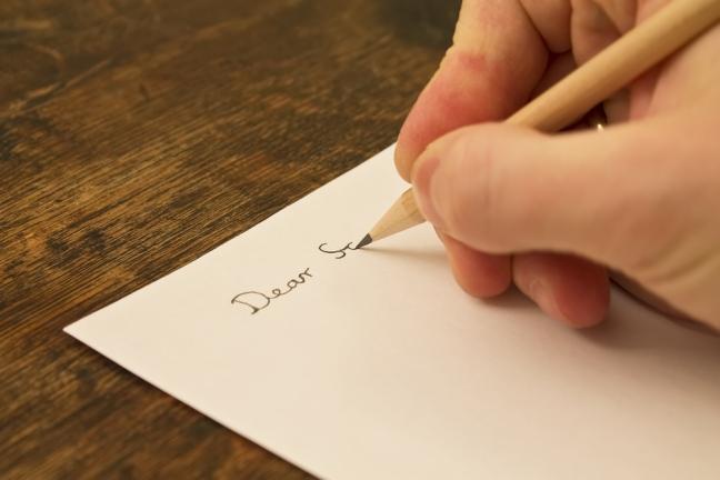 Bild einer Hand, die einen Brief schreibt