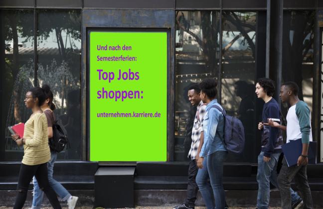 """Studenten passieren in Fußgängerzone eine Plakatfläche. """"Und nach den Semesterferien: Top Jobs shoppen: unternehmen.karriere.de"""""""