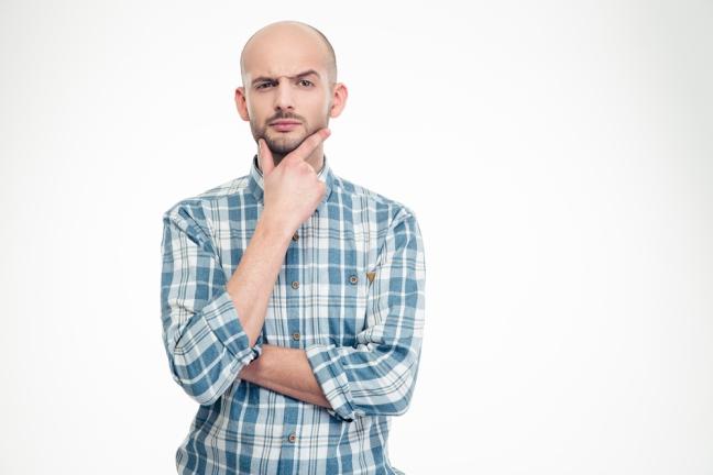 Junger Mann in Hemd fasst sich ans Kinn, zieht die Augenbraue hoch und schmunzelt