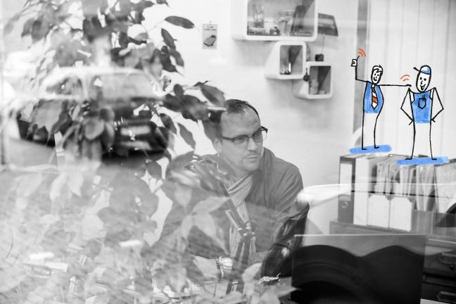 Jan im Büro, durch die Scheibe, auf der Scheibe eine Illustration von einem Chef, der dem Mitarbeiter auf die Schulter klopft