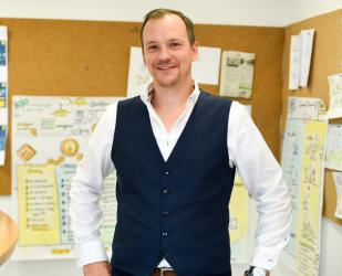 Jan Willand, Employer Branding Experte und Inhaber von menschmark, im Büro vor einer riesigen Pinnwand