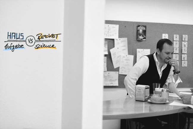 Jan im Büro, bei der Arbeit, an der Wand ein Bild Hausaufgabe vs Rocket Science