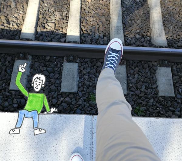 Ein Mann macht einen Schritt über die Bahnsteigkante. Dazu ein illustriertes Männchen mit erhobenem Zeigefinger: Mind the gap!