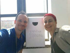 Jan Willand und San Ra Wickert mit dem Employer Standing Schild