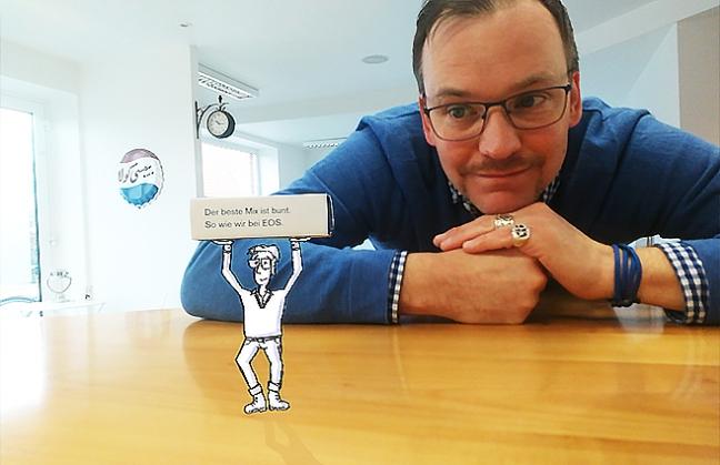 Jan stützt den Kopf auf eine Arbeitsplatte und schaut auf ein illustriertes Männchen, dass eine Smartiespackung hoch hält, auf der geschrieben steht: Der beste Mix ist bunt. So wie wir bei EOS.