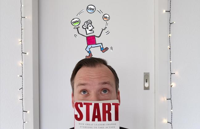 Jan vor einer weißen Wand, das Buch Start with Why in der Hand, eine illustrierte Figur auf dem Kopf, die mit dem Golden Circle jongliert