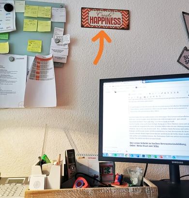 Jans Blechschild mit der Aufschrift Create Happiness über seinem Schreibtisch